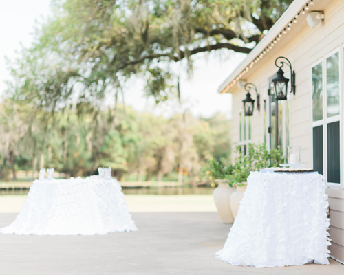 Tables On A Deck With White Tablecloths