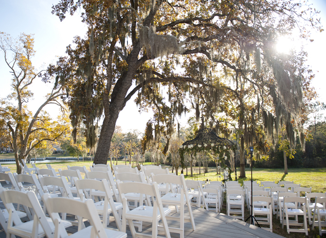 Rows Of White Chairs On Deck Facing Gazebo And Bayou