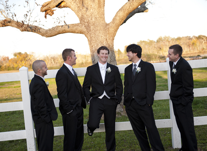 Men In Tuxedos Leaning Against White Picket Fence